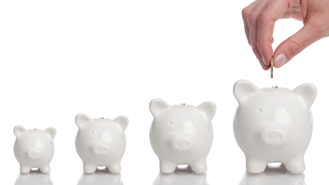 Hand inserting money into piggy banks