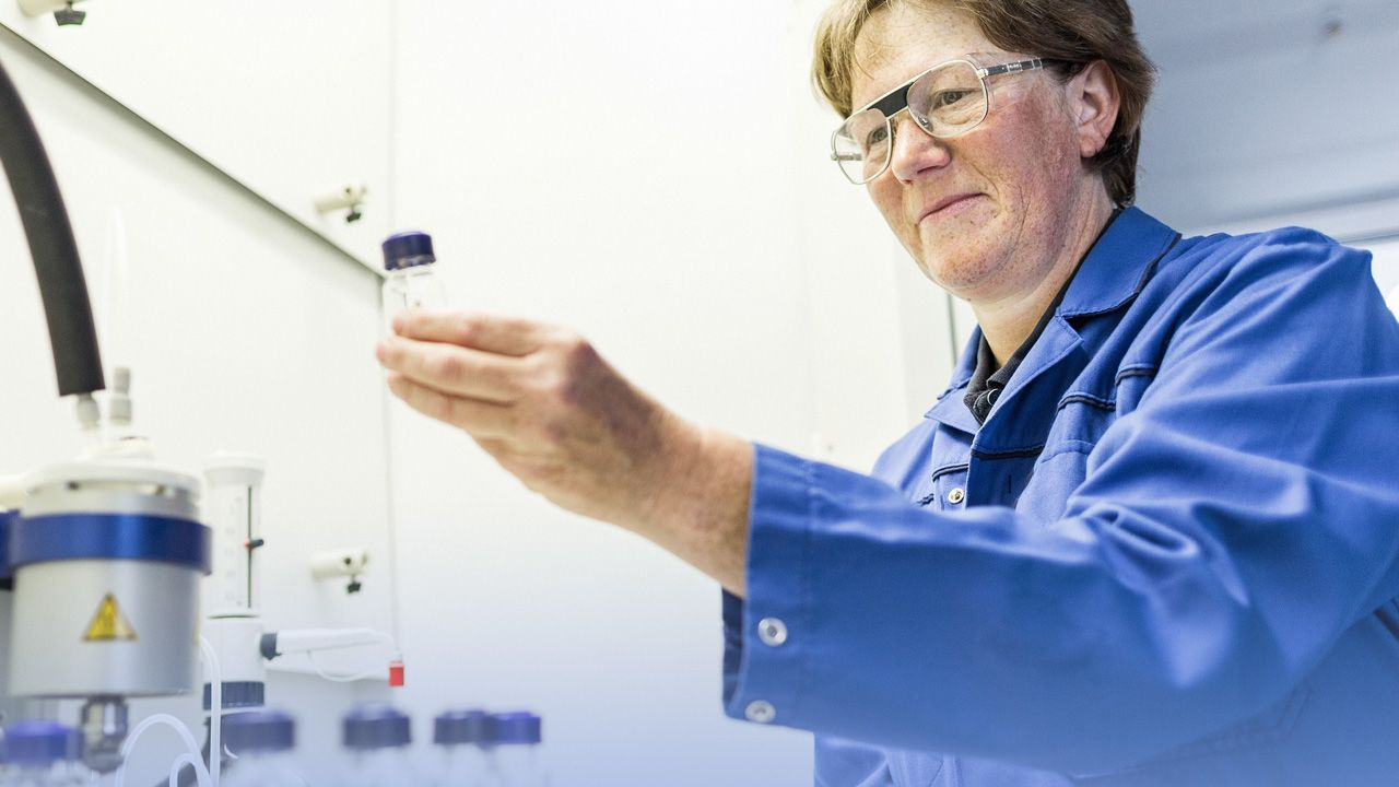 Laboratory technician observing container with sample in her hand